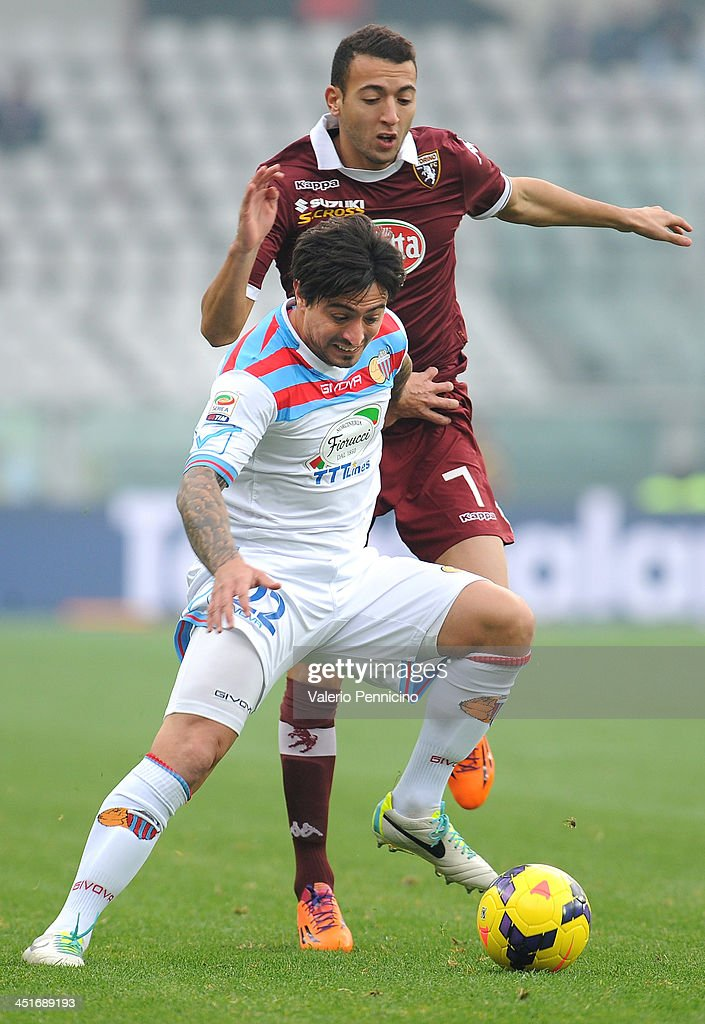 Pablo Alvarez of Calcio Catania competes for the ball with Omar El Kaddouri (R) of Torino FC during the Serie A match between Torino FC and Calcio Catania at Stadio Olimpico di Torino on November 24, 2013 in Turin, Italy.