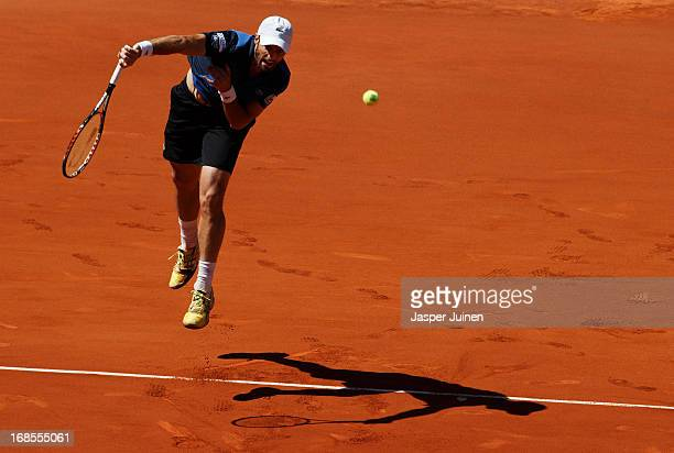Pablo Andujar of Spain jumps to serve the ball to Rafael Nadal of Spain during his semifinal match on day eight of the Mutua Madrid Open tennis...