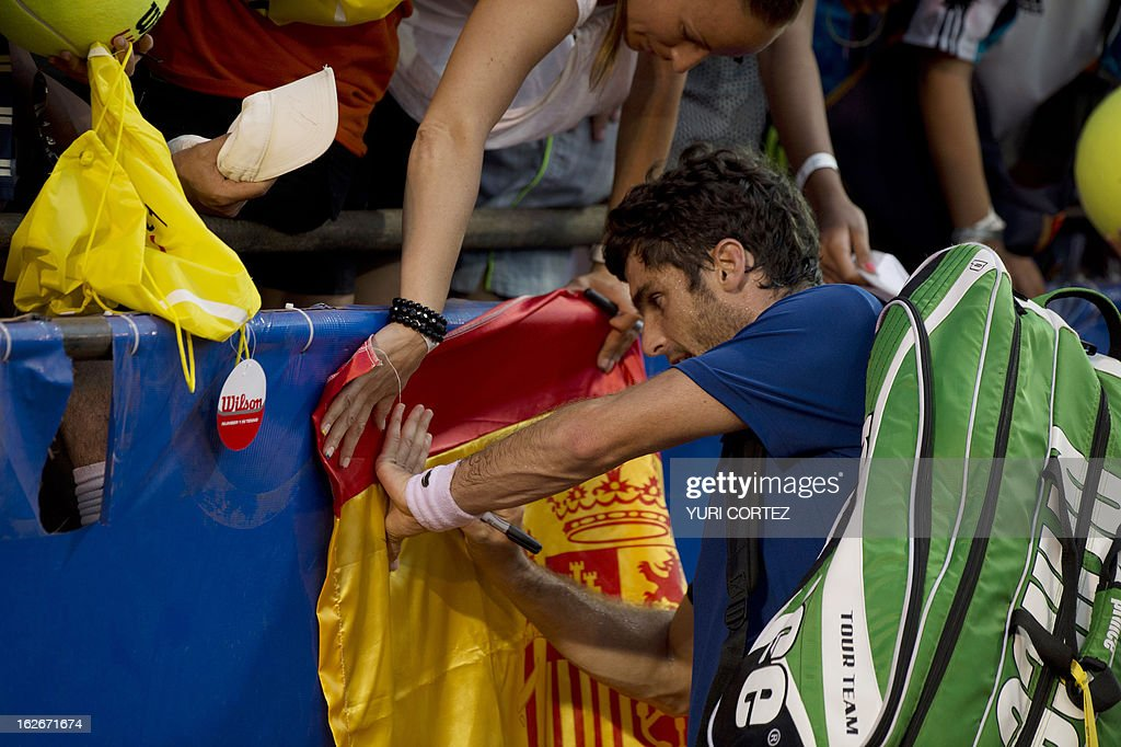 Pablo Andujar of Spain sings on his national flag after winning the game against Dusan Lajovic of Serbia at the Mexican Tennis Open on February 25, 2013 in Acapulco, Guerrero state, Mexico. AFP PHOTO/ Yuri CORTEZ
