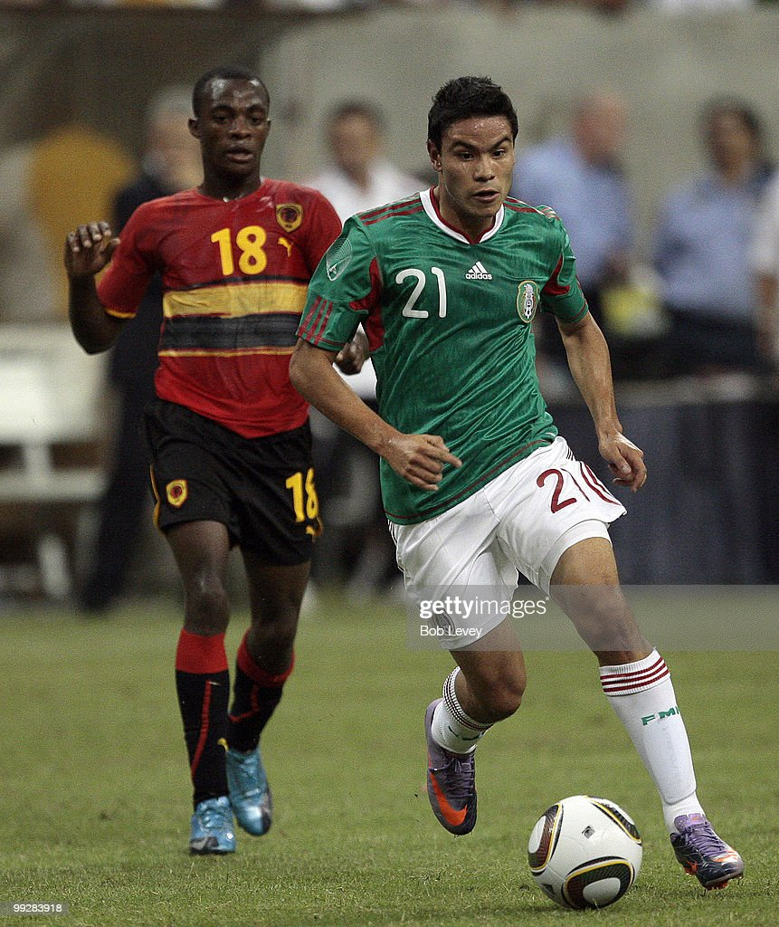 Pablo Barrera #21 of Mexico brings the ball up the field as he is pursued by Hermenegildo Bartolomeu #18 of Angola at Reliant Stadium on May 13, 2010 in Houston, Texas.