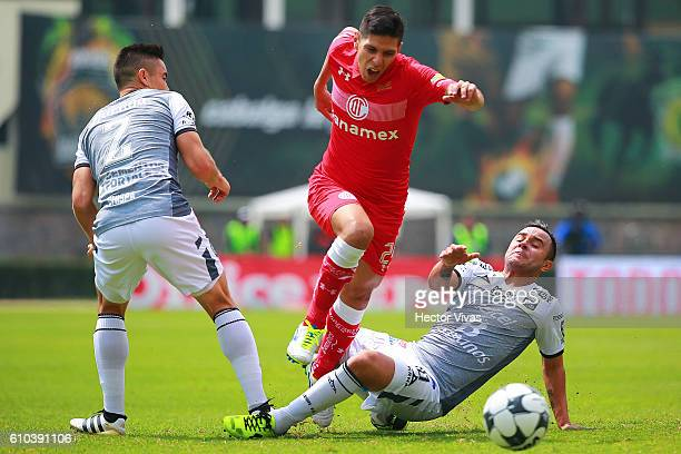Pablo Barrientos of Toluca struggles for the ball with Luis Montes and Efrain Velarde of Leon during the 11th round match between Toluca and Leon as...