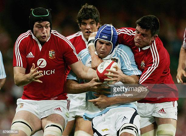 Pablo Bouza of Argentina is wrapped up by Michael Owen and Martin Corry of the Lions during the Rugby Union International Match between the British...