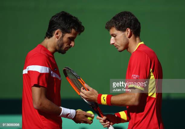Pablo Carreno Busta and Feliciano Lopez of Spain talk tactics against Dom Inglot and Jamie Murray of Great Britain in the doubles during day two of...