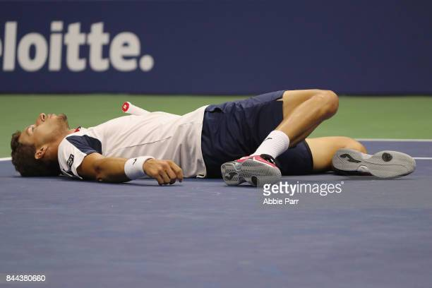 Pablo Carreno Busta of Spain falls to the court in the fourth set against Kevin Anderson of South Africa during their Men's Singles Semifinal match...