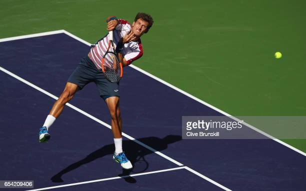 Pablo Carreno Busta of Spain plays a smash against Pablo Cuevas of Uruguay in their quarter final match during day eleven of the BNP Paribas Open at...
