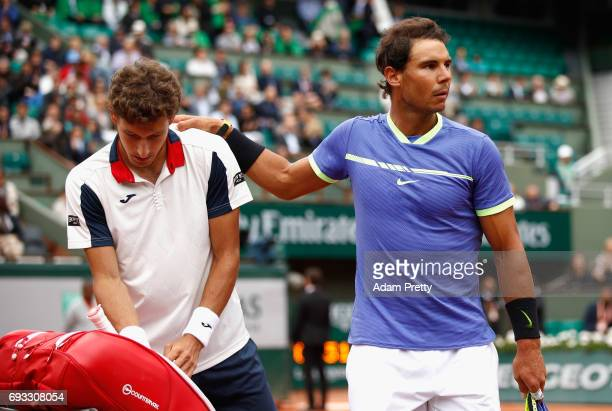 Pablo Carreno Busta of Spain speaks with his opponant Rafael Nadal of Spain after he retires due to an injury in the mens singles quarter finals...
