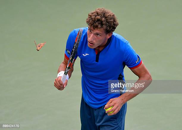 Pablo Carreno Busta of Spain watches a butterfly float past as he prepares to serve to Andrey Kuznetsov of Russia during the WinstonSalem Open at...