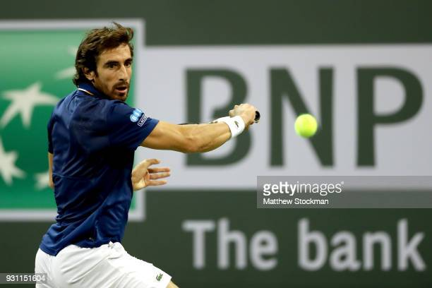Pablo Cuevas of Uraguay returns a shot to Dominic Thiem of Austria during the BNP Paribas Open at the Indian Wells Tennis Garden on March 12 2018 in...