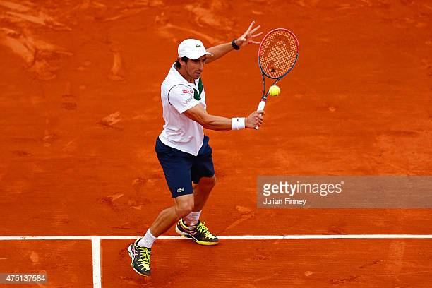 Pablo Cuevas of Uruguay plays a backhand in his Men's Singles match against Gael Monfils of France on day six of the 2015 French Open at Roland...