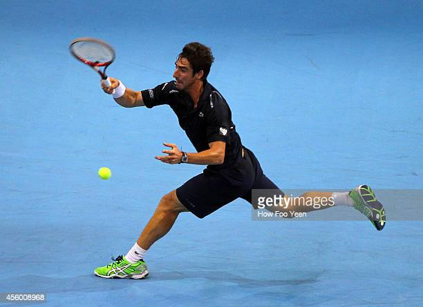 Pablo Cuevas of Uruguay plays a return shot to Ivan Dodig of Crotia during the Malaysian Open at Putra Stadium on September 24 2014 in Kuala Lumpur...