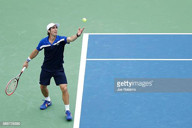 Pablo Cuevas of Uruguay serves to Sam Querrey of the United States during the first round on Day 3 of the Western Southern Open at the Lindner Family...