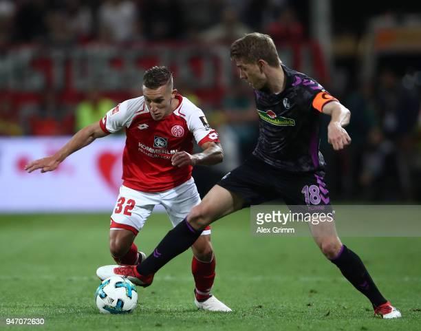 Pablo de Blasis of Mainz is challenged by Nils Petersen of Freiburg during the Bundesliga match between 1 FSV Mainz 05 and SportClub Freiburg at Opel...