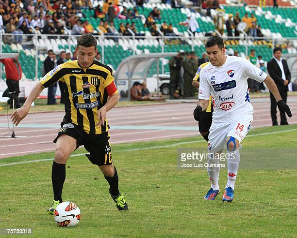 Pablo Escobar of The Strongest competes for the ball with Marcos Melgarejo of Club Nacional during a match between The Strongest and Club Nacional as...