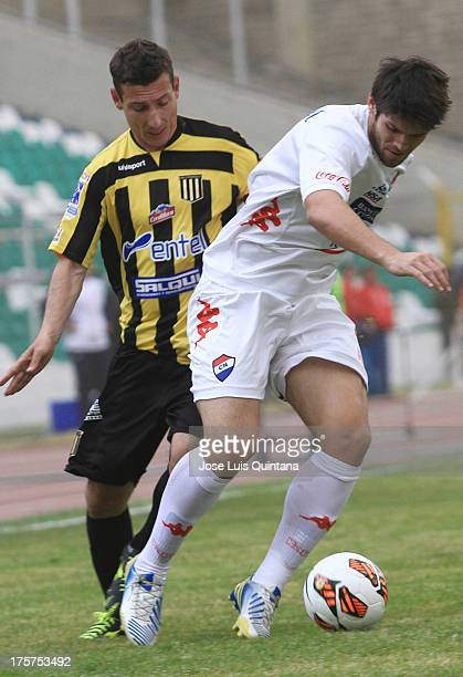 Pablo Escobar of The Strongest competes for the ball with Marcos Miers of Club Nacional during a match between The Strongest and Club Nacional as...