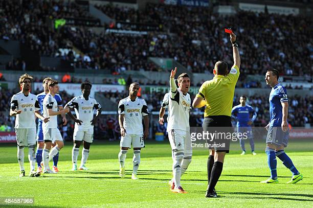 Pablo Hernandez of Swansea remonstrates with Referee Phil Dowd as he shows the red card to Chico Flores of Swansea during the Barclays Premier League...