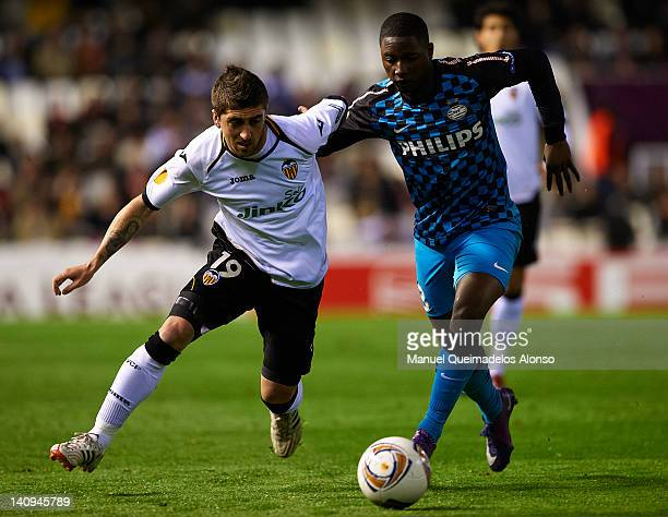 Pablo Hernandez of Valencia competes for the ball with Wilfred Bouma of PSV Eindhoven during the UEFA Europa League Round of 16 first leg match...