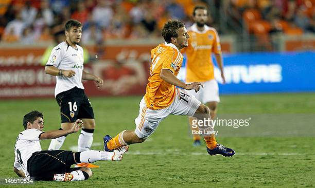 Pablo Hernandez of Valencia trips up Colin Rolfe of the Houston Dynamo in the second half at BBVA Compass Stadium on May 31 2012 in Houston Texas...