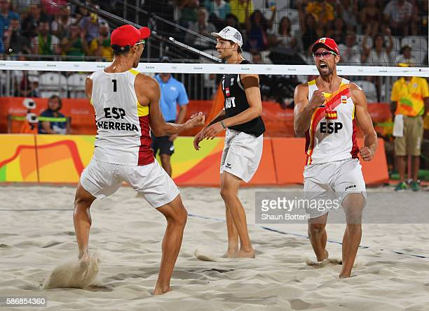Pablo Herrera Allepuz and Adrian Gavira Collado of Spain celebrate victory during the Men's Beach Volleyball preliminary round Pool F match against...