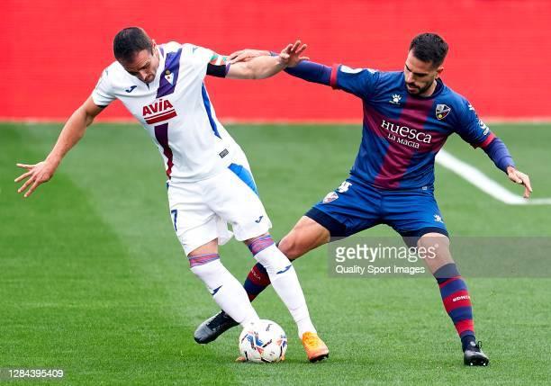 Pablo Insua of SD Huesca competes for the ball with Kike Garcia of SD Eibar during the La Liga Santander match between SD Huesca and SD Eibar at...