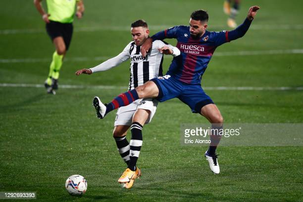 Pablo Insua of SD Huesca competes for the ball with Roger Marti of Levante UD during the La Liga Santander match between SD Huesca and Levante UD at...