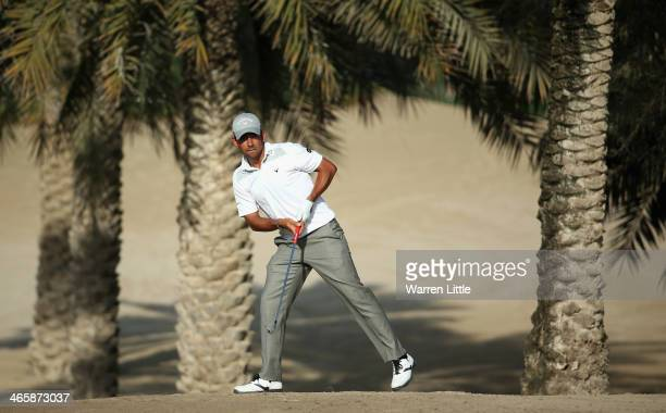 Pablo Larrazabal of Spain plays his second shot on the 14th hole during the first round of the 2014 Omega Dersert Classic on the Majlis Course at the...