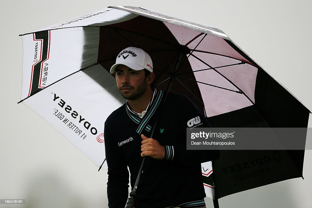Pablo Larrazabal of Spain shelters from the rain under his umbrella on the 14th green during Day 2 of the KLM Open at Kennemer G & CC on September 13, 2013 in Zandvoort, Netherlands.