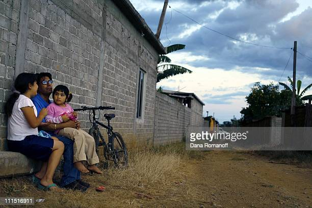 Pablo Lopez sits outside of his home with his daughters Marisol and Marlyn on October 26 2006 in the town of San Pablo Huixtepec Pablo has been...