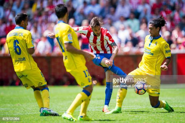Pablo Mauricio Lemos of UD Las Palmas duels for the ball with Duje Cop of Real Sporting de Gijon during the La Liga match between Real Sporting de...