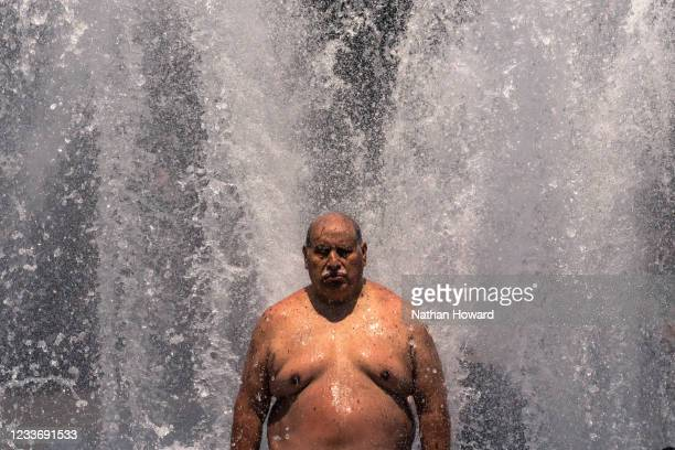 Pablo Miranda cools off in the Salmon Springs Fountain on June 27, 2021 in Portland, Oregon. Record breaking temperatures lingered over the Northwest...