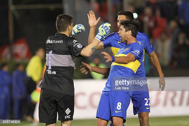 Pablo Perez and Juan Insaurralde of Boca Juniors congratulate Agustin Orion after making a save on a penalty during a first leg match between Cerro...