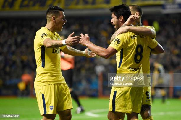 Pablo Perez of Boca Juniors celebrates with teammates Cristian Pavon and Dario Benedetto after scoring the second goal of his team during a match...