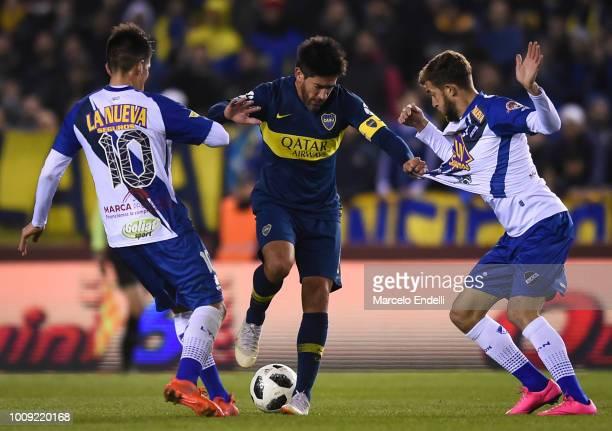 Pablo Perez of Boca Juniors fights for the ball with Gaspar Gentile and Cristian Canuhe of Alvarado during a match between Boca Juniors and Alvarado...