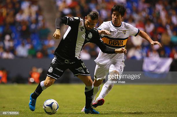 Pablo Perez of Boca Juniors struggles for the ball with Flavio Santos of Puebla during the friendly match between Puebla and Boca Juniors at...