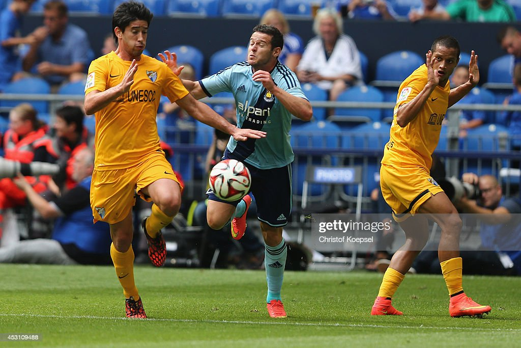 Pablo Perez of Malaga (L) and Jose Rosales of Malaga (R) challenge Mauro Zarate of Malaga (C) during the match between FC Malaga and West Ham United as part of the Schalke 04 Cup Day at Veltins-Arena on August 3, 2014 in Gelsenkirchen, Germany.