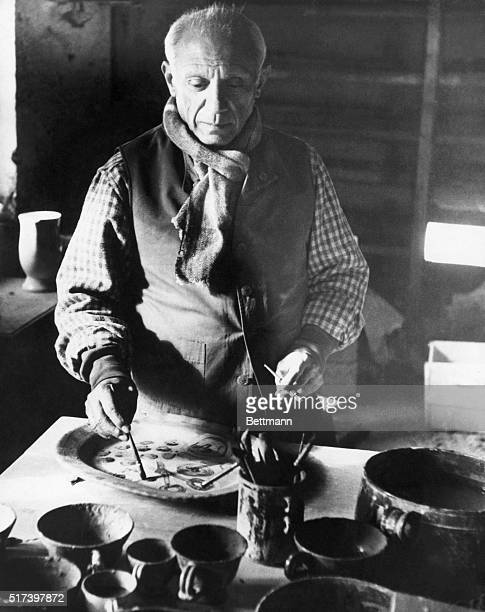 Pablo Picasso is shown painting decorations on a plate in his pottery studio at his villa on the French Riviera 1948