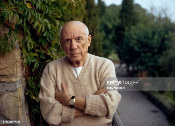 Pablo Picasso standing by a green fern with folded arms wearing a cashmere sweater