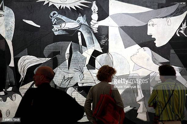 Pablo Picasso's Guernica in Reina Sofia National Art Museum (Museo Nacional de Arte Reina Sofia) with visitors in foreground.