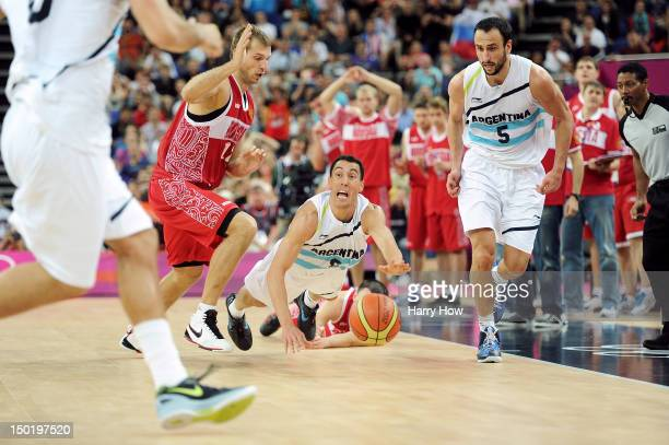 Pablo Prigioni of Argentina dives for a loose ball past Sergey Monya of Russia during the Men's Basketball bronze medal game between Russia and...