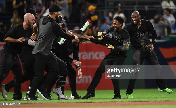 Pablo Reyes of the Pittsburgh Pirates is mobbed by teammates after hitting a walk-off RBI single to left field giving the Pittsburgh Pirates a 3-2...