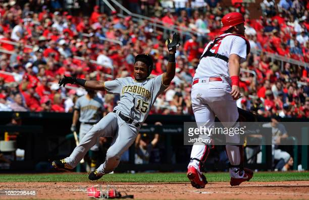 Pablo Reyes of the Pittsburgh Pirates slides in at home to score as Carson Kelly of the St Louis Cardinals waits for the throw during the sixth...