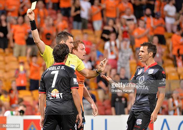 Pablo Sanchez of Adelaide is given a yellow card by referee Jarred Gillett during the round 16 ALeague match between the Brisbane Roar and Adelaide...