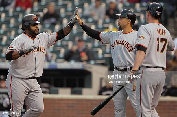 Pablo Sandoval of the San Francisco Giants is welcomed home by Carlos Beltran and Aubrey Huff of the Giants after his two run homerun off of starting...