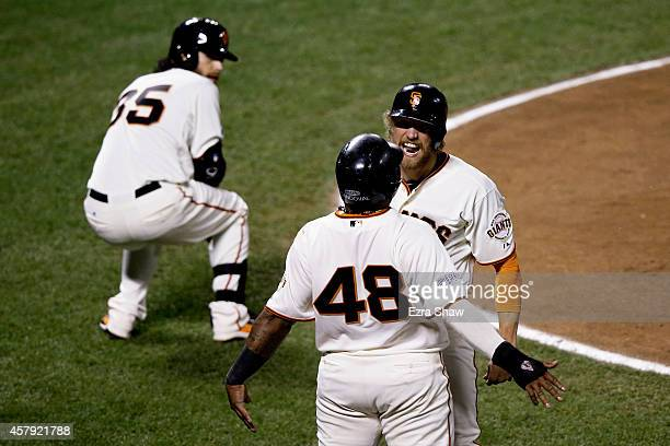 Pablo Sandoval and Hunter Pence of the San Francisco Giants celebrate after both scoring in the eighth inning against the Kansas City Royals during...
