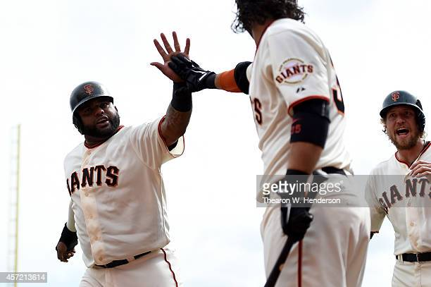 Pablo Sandoval Brandon Crawford and Hunter Pence of the San Francisco Giants celebrate after Sandoval and Pence score in the first inning against the...