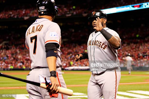 Pablo Sandoval celebrates with Gregor Blanco after scoring on a single by Travis Ishikawa of the San Francisco Giants in the second inning against...