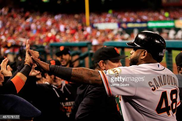 Pablo Sandoval is welcomed to the dugout after scoring on a single by Travis Ishikawa of the San Francisco Giants in the second inning against the St...