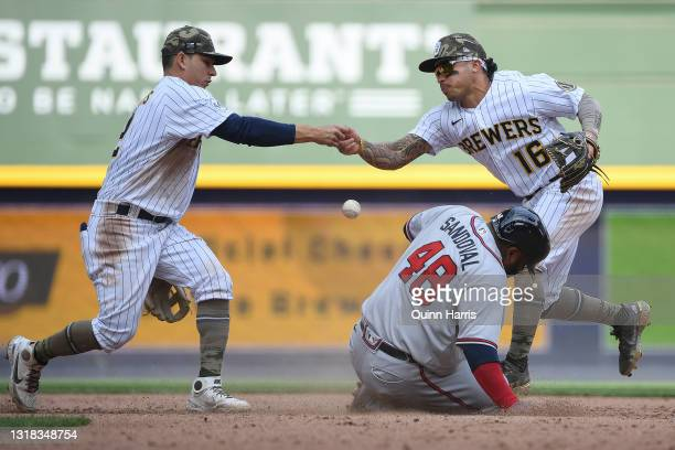 Pablo Sandoval of the Atlanta Braves is safe after Luis Urias and Kolten Wong of the Milwaukee Brewers commit an error at second base in the seventh...