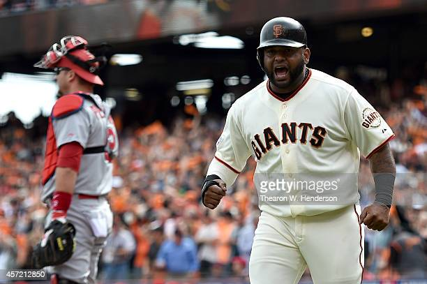 Pablo Sandoval of the San Francisco Giants celebrates after scoring in the first inning against the St Louis Cardinals during Game Three of the...