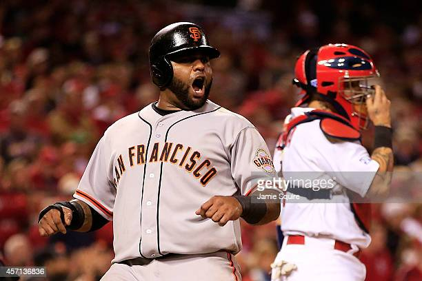 Pablo Sandoval of the San Francisco Giants celebrates scoring on a single by Hunter Pence in the sixth inning as Yadier Molina of the St. Louis...