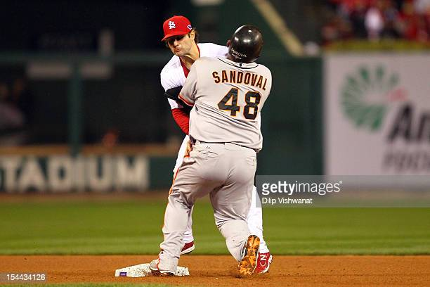 Pablo Sandoval of the San Francisco Giants crashes into Pete Kozma of the St Louis Cardinals after pitcher Lance Lynn of the Cardinals has a throwing...